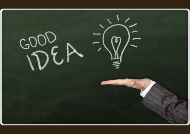 The chalk board illustrating good idea, with a hand holding a light bulb.