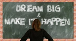 the chalk board illustrating dream big, and make it happen, with a student in front of it.