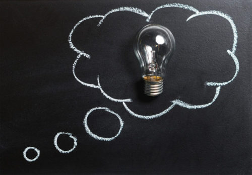 Chalk board illustration of a light bulb, depicting ideas.