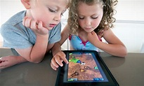 The picture of two little kids, playing with their fun learning tablet.