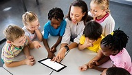 The picture of a teacher and six of her students engaging a fun learning tablet.