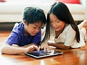 The picture of a little boy and girl engaging with their fun learning tablet.