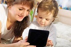 The picture of a mother alongside of hear very young child, still in her toddler years, engaging a fun learning device.